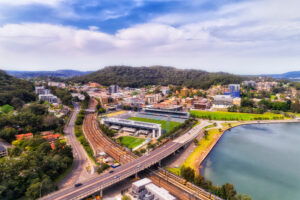 Gosford town in the middle of the Central coast of Austrlia - aerial view above local sports stadium and Central coast highway near train station between hill ranges on waterfront.